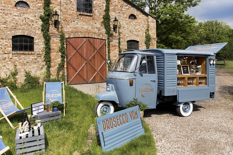 Niebieski prosecco van z stojącym u koła banerem przed salą weselą
