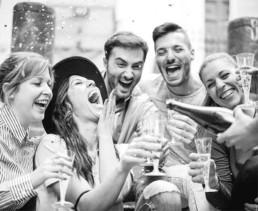 Grupa radosnych młodych ludzi sięgająca po wino musujące z baru mobilnego podczas imprezy