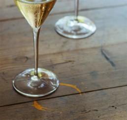 Kieliszek białego wina z odciskiem Culaccino na drewnianym stole