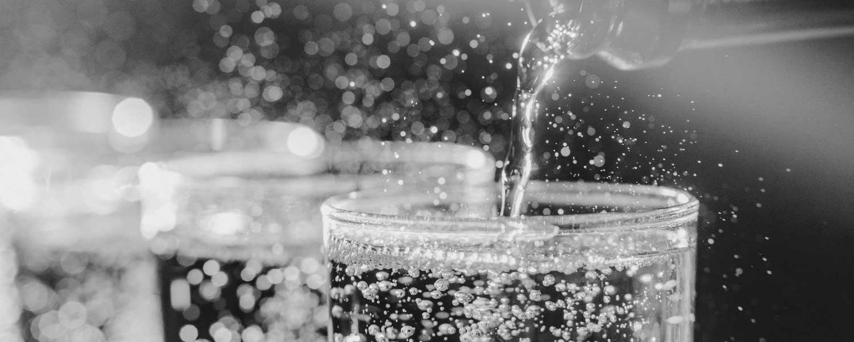 Prosecco nalewane z butelki do kieliszków i dużo pryskających bąbelków wina wokoło