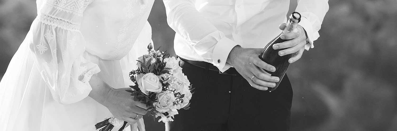 Młoda para trzymająca w ręku wino prosecco z baru mobilnego podczas wesela