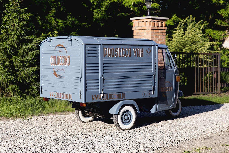 Niebieski prosecco van stylizowany na włoskiego trójkołowca przy bramie wjazdowej do posesji