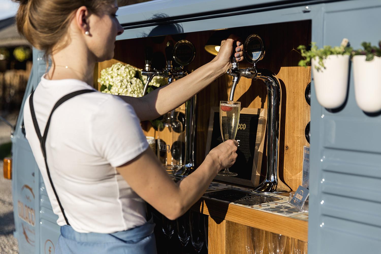 Kelnerka nalewająca prosecco z nalewaka do kieliszka