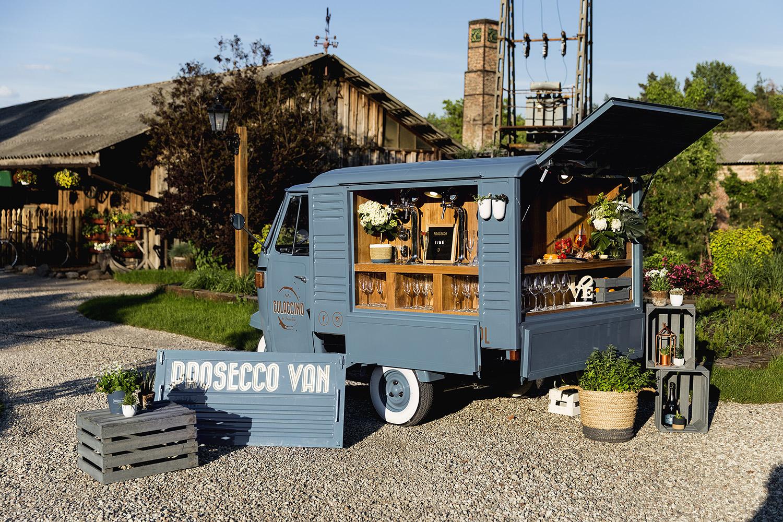 Niebieski prosecco van z otwartym barkiem dla gości