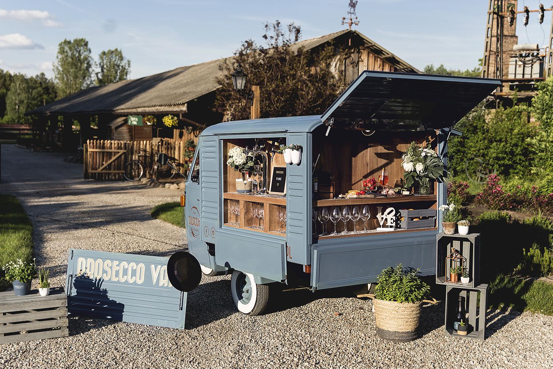 Mobilny bar z winem prosecco ulokowany przy wjeździe do sali weselnej