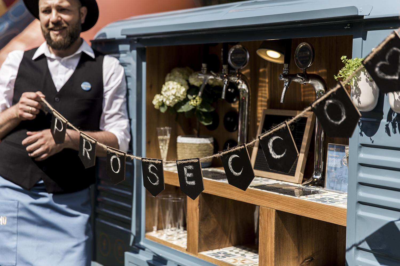 Kelner trzymający baner przy prosecco vanie