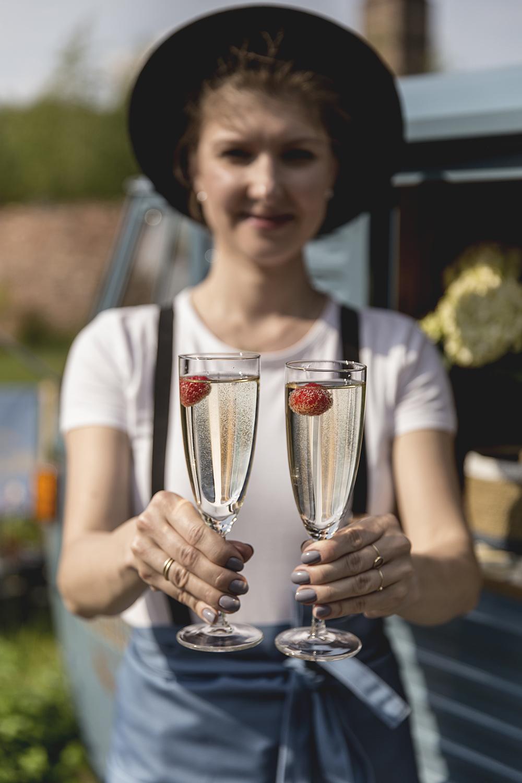 Kelnerka podająca dwa kieliszki z winem prosecco z truskawkami